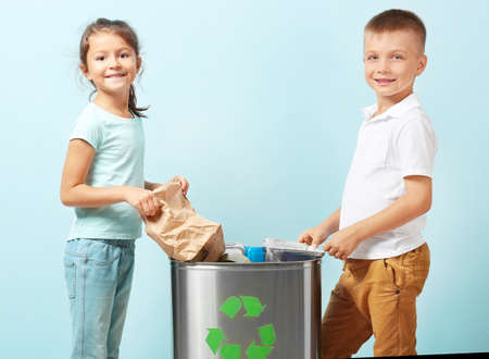 Little children throwing garbage into litter bin on color background. Recycling concept
