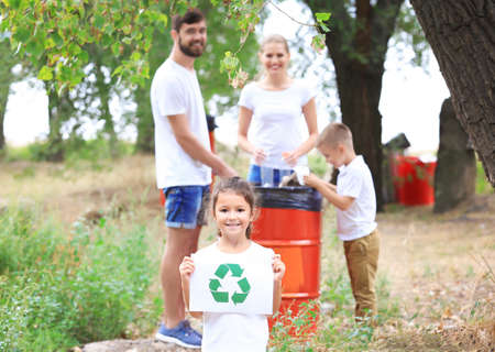 Family throwing garbage into litter bin outdoors. Recycling concept