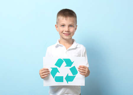 Little boy holding paper sheet with recycling symbol on color background