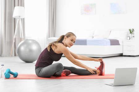 Jonge sportieve vrouw die met laptop thuis yoga beoefent Stockfoto