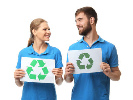 Young couple holding paper sheets with recycling symbol on white background