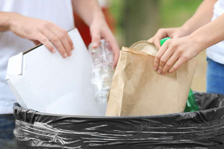 Young couple throwing garbage into litter bin outdoors, closeup
