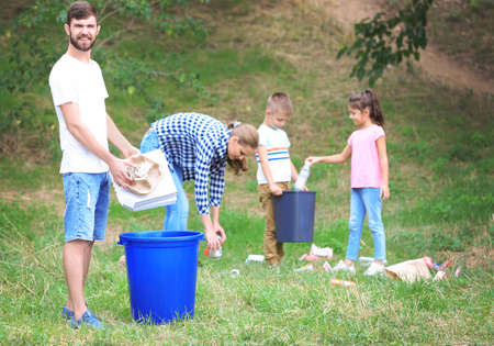Family collecting garbage outdoors. Recycling concept Stock Photo
