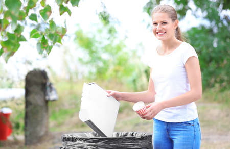 Young woman throwing garbage into litter bin outdoors