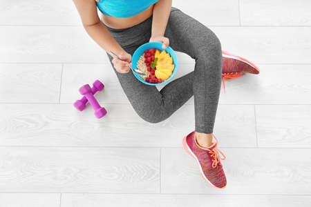 Young woman in sportswear eating oatmeal while sitting on floor Stock Photo