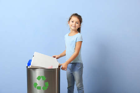 Little girl throwing garbage into litter bin on color background. Recycling concept