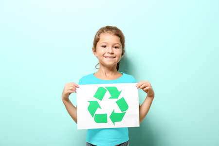 Little girl holding paper sheet with recycling symbol on color background