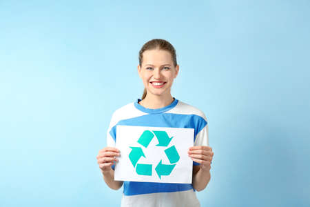 Young woman holding paper sheet with recycling symbol on color background Stock Photo