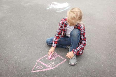 Little girl drawing house with chalk on asphalt
