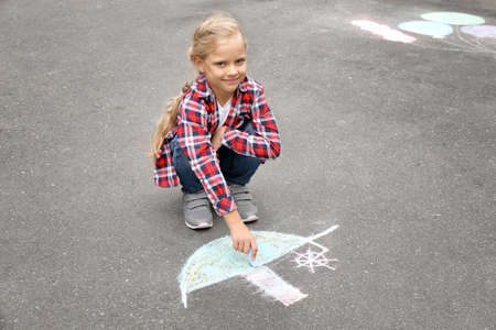 Little girl drawing ship with chalk on asphalt