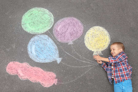 Little boy lying near chalk drawing of air balloons on asphalt