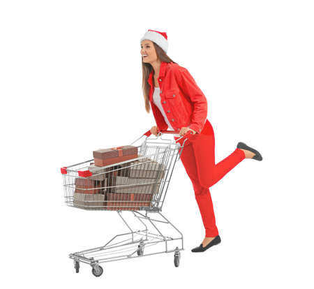 Beautiful young woman in Santa Claus hat with cart full of gifts on white background. Christmas shopping concept Stock Photo