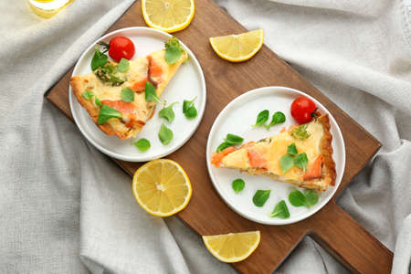 Plates with pieces of salmon quiche pie on wooden board