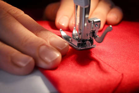 Woman sewing on machine, closeup