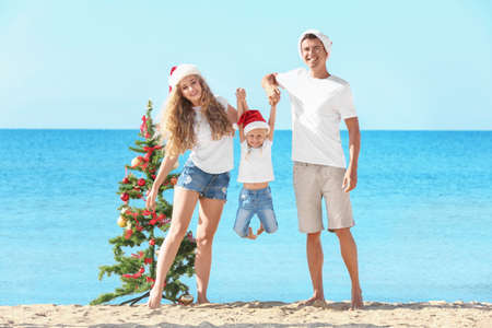 Happy family and Christmas tree on beach Banque d'images - 101372240