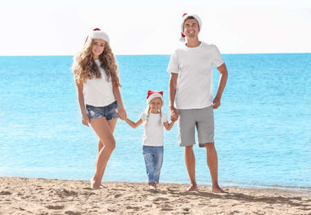 Young couple with girl on beach. Christmas celebration concept Banque d'images