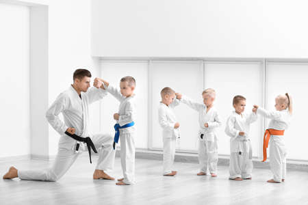Little children with instructor practicing karate in dojo