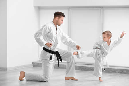 Little boy with instructor practicing karate in dojo