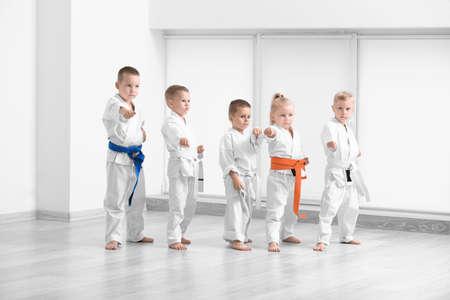 Małe dzieci ćwiczą karate w dojo