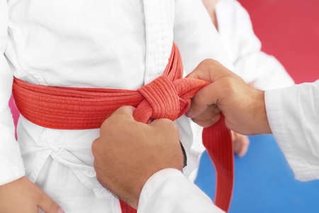 Karate instructor tying belt on childs waist, closeup Stock Photo
