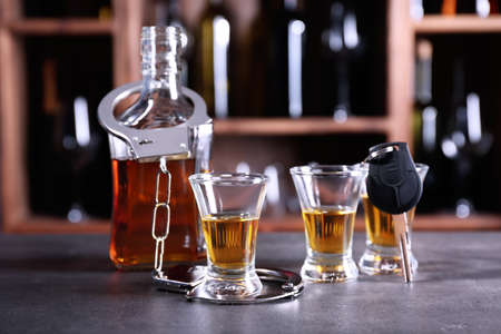 Glassware of alcohol with handcuffs and car key on table in bar. Dont drink and drive concept