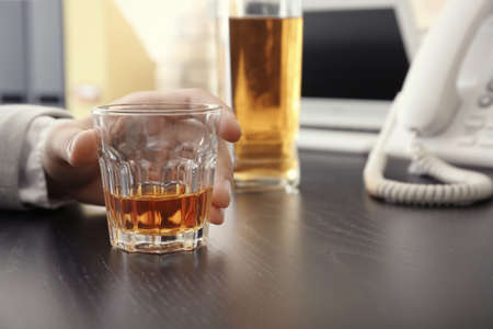 Man with glass of whiskey indoors. Alcohol dependence concept