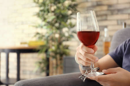 Man in handcuffs with glass of wine indoors. Alcohol dependence concept