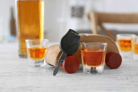 Composition with alcohol, toy and car key on wooden table. Dont drink and drive concept