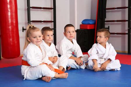 Kleine Kinder tragen karategi in Dojo