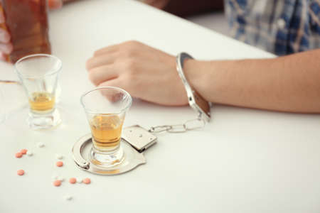 Man in handcuffs sitting at table with glass of brandy and drugs. Alcohol dependence concept