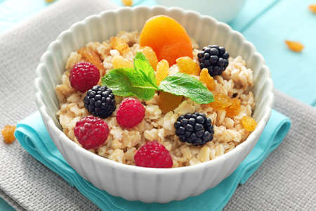 Tasty oatmeal with berries and fruit in bowl on table