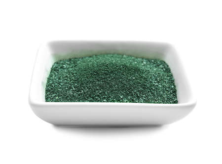 Bowl with spirulina powder on white background