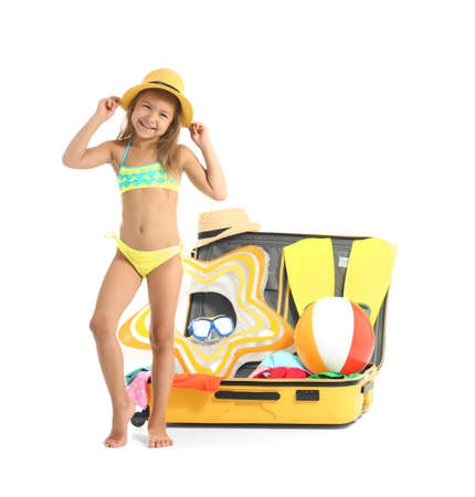 Adorable little girl in swimsuit near suitcase on white background