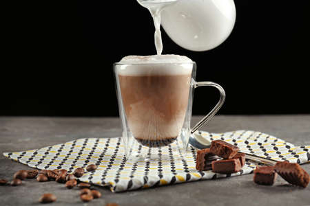 Pouring milk into cup with latte macchiato on black background