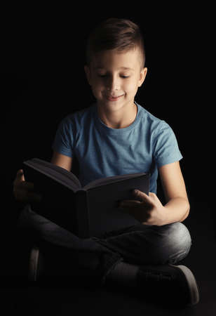 Cute little boy reading book on dark background