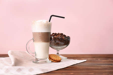 Glass with latte macchiato on table against color background Stock Photo