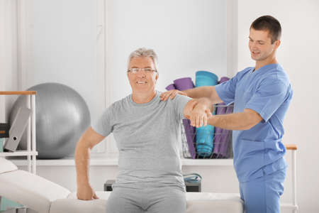 Physiotherapist working with senior patient in modern clinic