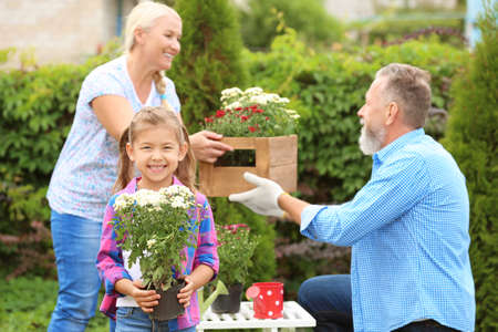 Little girl holding blooming plant while her grandparents working in garden Stock Photo