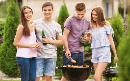 Jóvenes amigos con fiesta de barbacoa en el jardín Foto de archivo