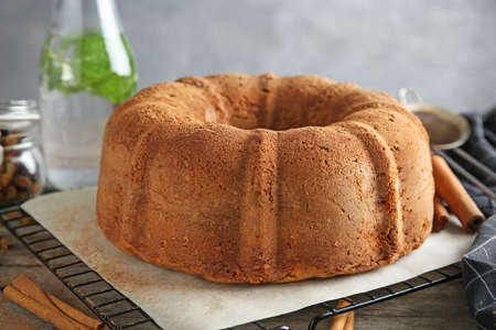 Baking rack with delicious cinnamon cake on table
