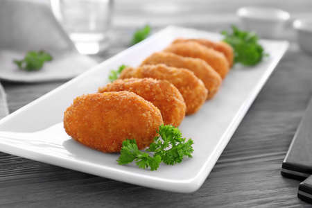 Plate with delicious salmon croquettes on table, closeup
