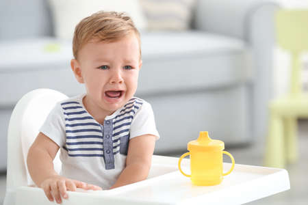 Adorable crying baby sitting in highchair at home