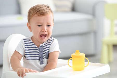 Schattige huilende baby in kinderstoel thuis zitten