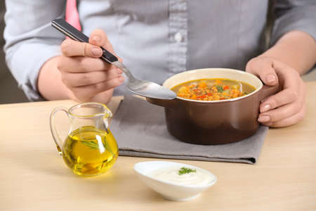 Woman eating tasty lentil soup at table