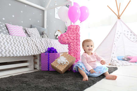 Cute baby with birthday presents sitting on floor at home