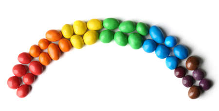 Colorful candies arranged as rainbow, isolated on white
