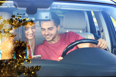 Beautiful young couple with mobile phone in car Stock Photo