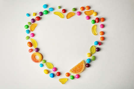 Colorful candies arranged as heart, isolated on white