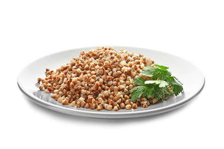 Plate with cooked buckwheat on white background