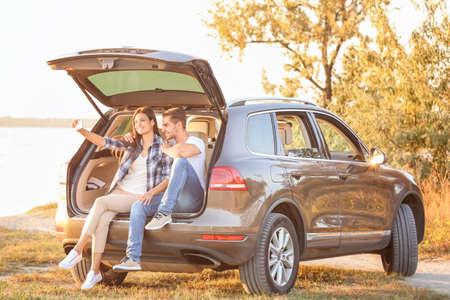 Beautiful young couple taking selfie in car trunk